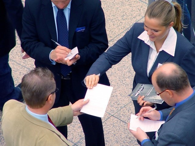 Image of a leader passing out leaflets to mentor their employees