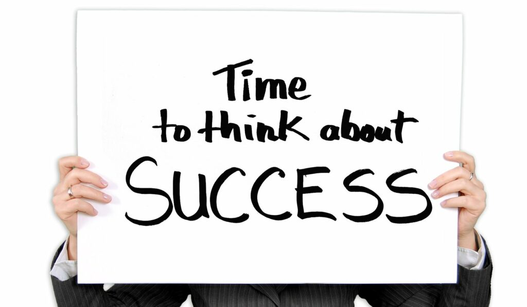 Image of a person holding a sign saying time to think about success for steps to create a vision statement section.