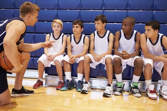 Image of a coach rallying and motivating his team for a game for the coaching leadership style.