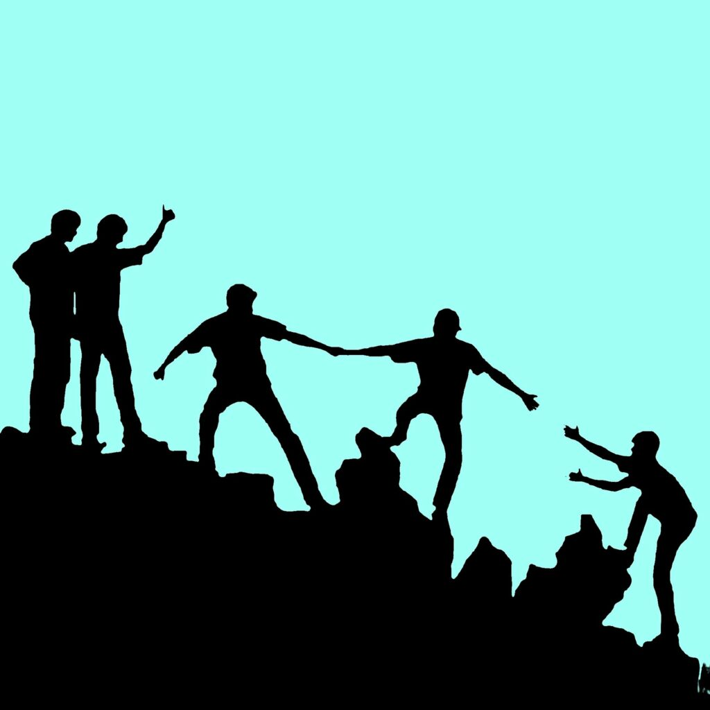 Image of people helping each other up a mountain representing the need for other people even while away from the office.