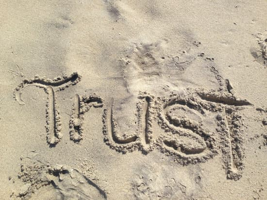 Image of trust written in the sand for the  how to delegate tip 1.