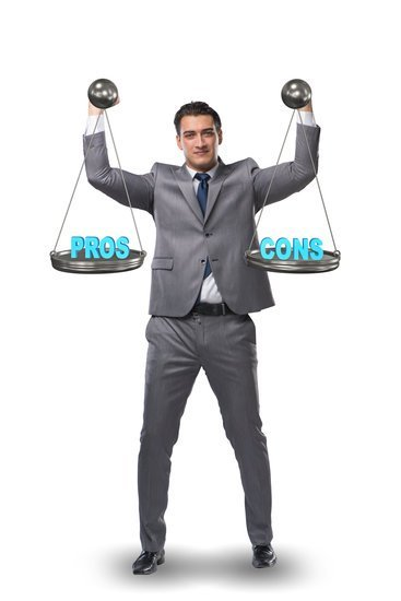 Image of  a man holding a scale with pros on one side and cons on the other for disadvantages of working from home.