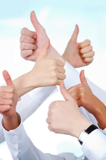 Image of many people giving thumbs up for positive mindset tip for teleworking.