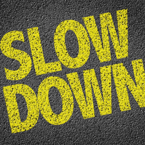 Image of the words slow down written on a road representing the need to not rush during a negotiation.