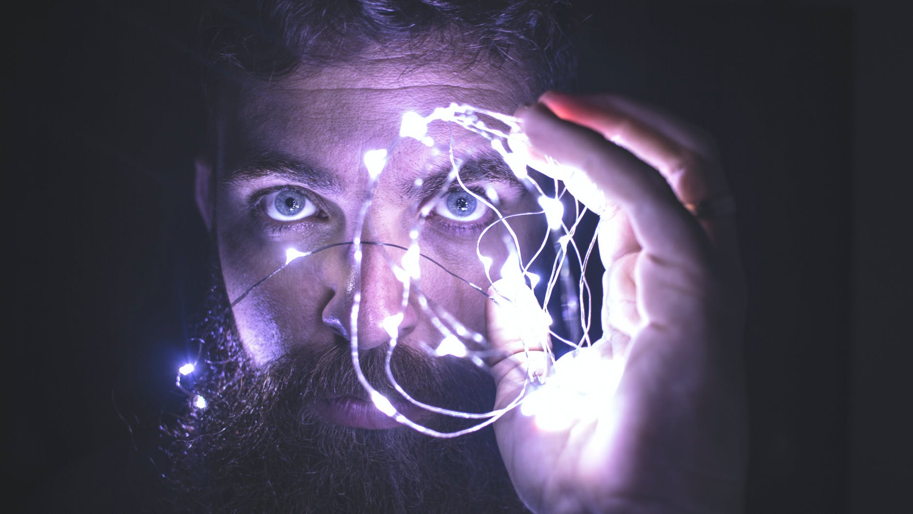 Image of a person holding string lights representing vision for team performance.