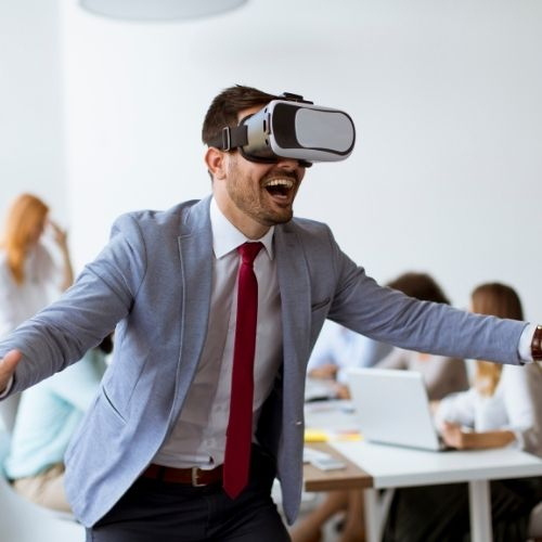 Image of busniess man wearing VR goggles for challenges section in virtual team building activities and virtual icebreakers article.