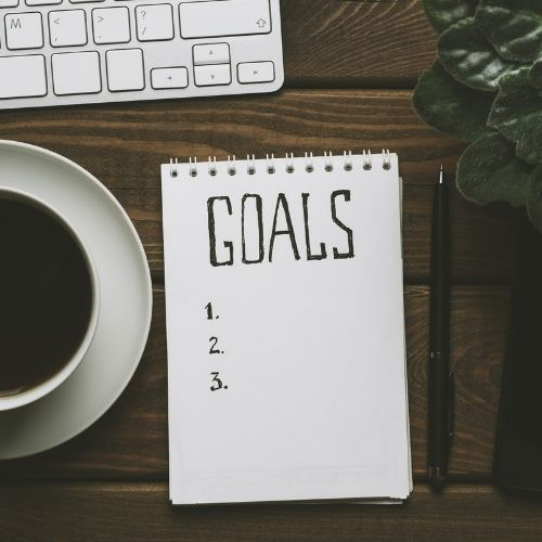 Image of coffee cup and notebook with goals on it for LinkedIn profile tips section 2.