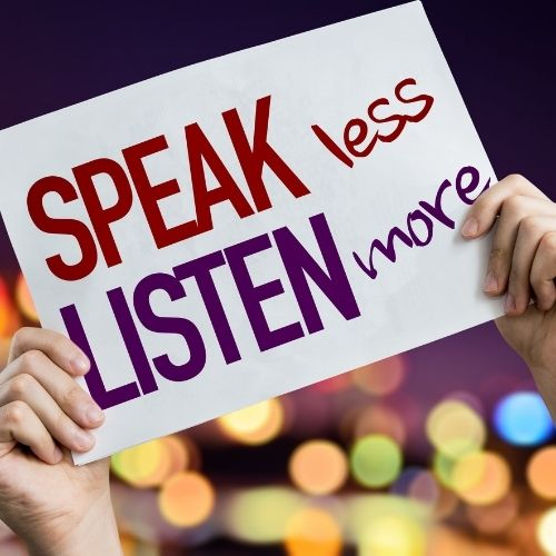 Image of a person holding up a sign saying speak more, listen less.