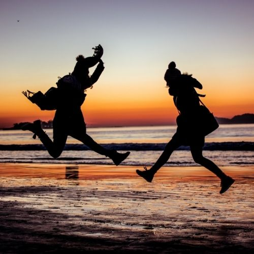 Image of 2 people jumping in joy