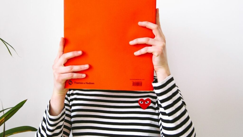 Image of a person hiding their face behind a folder.