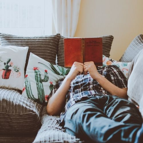 Image of a person in their comfort zone reading a book.
