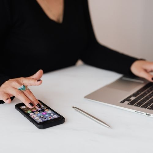 Image of a person using a smartphone and a laptop.