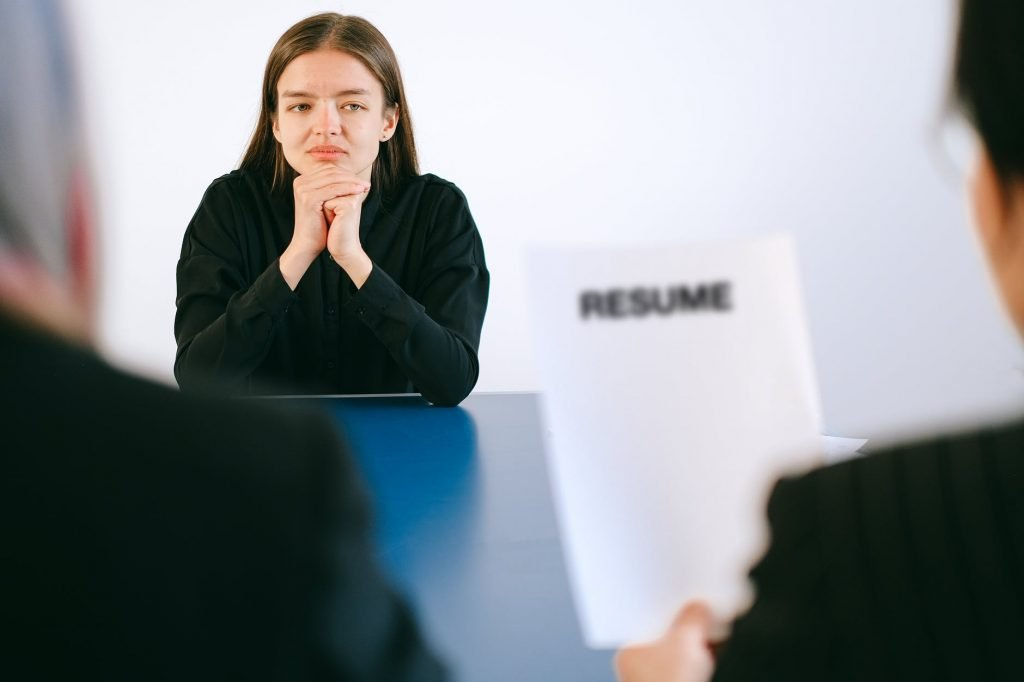 Image of man looking at a resume as he interviews a young lady.