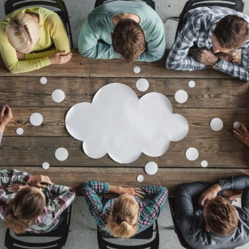 Image of people around a table in a meeting for steps for planning a meeting section.