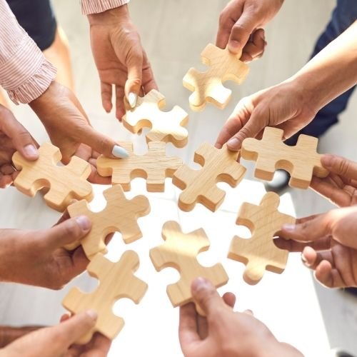 Image of a team holding puzzle pieces for team building to boost morale on your team.