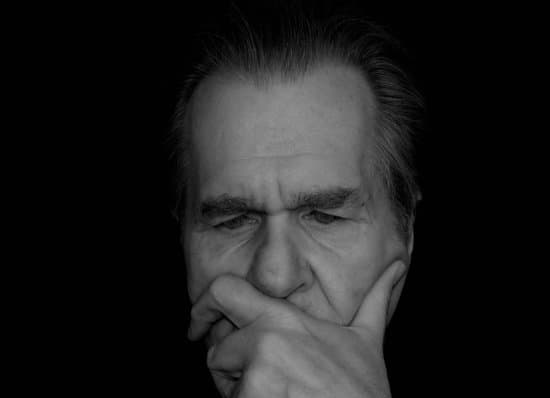Image of a man with his hands on his chin thinking about what decision to make representing new supervisor, boss, leader, manager, first time supervisor overthinking.