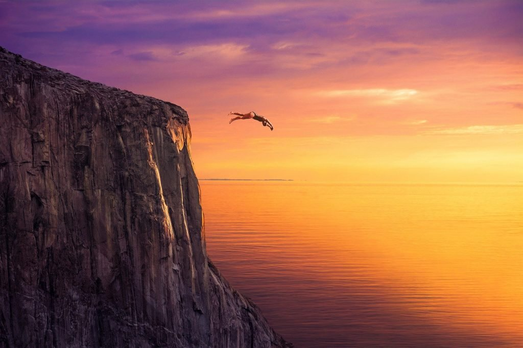 Image of a person jumping off a cliff representing the feeling when you step out of our comfort zone.