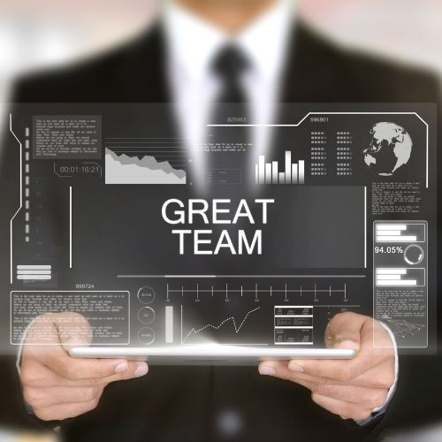 Image of business professional holding a tablet displaying great team for virtual team benefits.