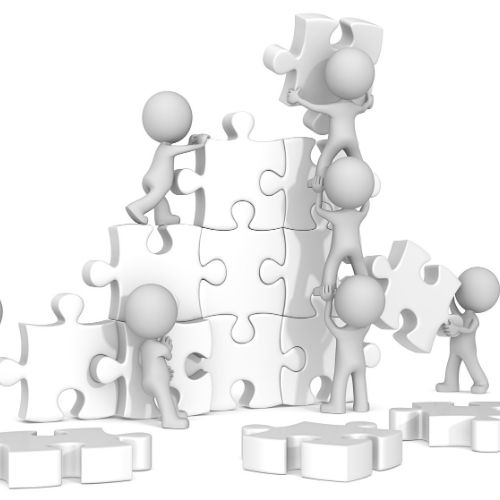 Image of workers putting puzzle pieces together representing team building games.