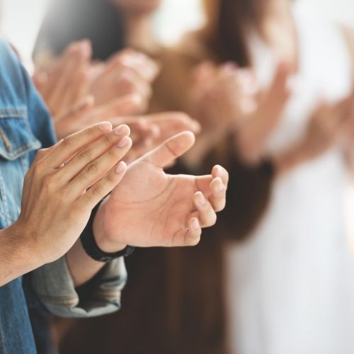Image of co-workers clapping for recognition virtual team building activity.
