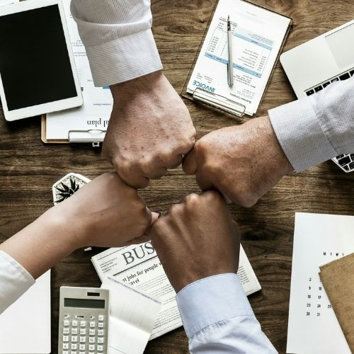 Image of four people fist bumping after successful meeting for tips for conducting an effective meeting section.