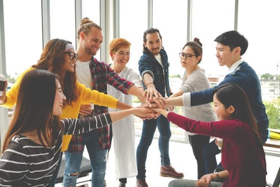 Image of co-workers putting their hands together in the middle of a circle after team building activities for work, team building games, team building exercises.