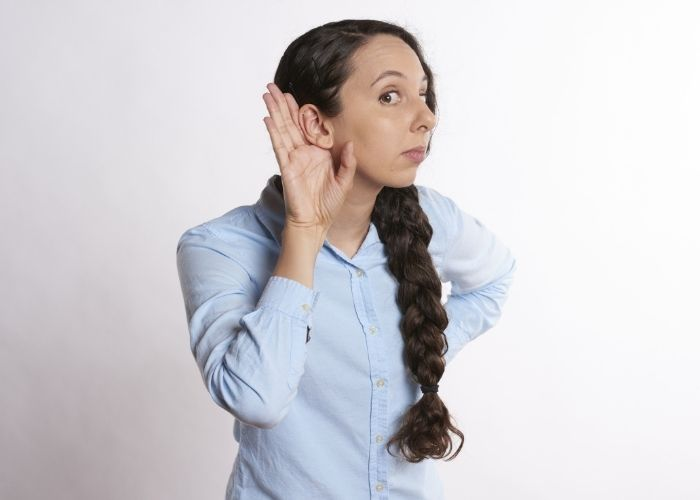 Image of a lady holding her hand to her ear for listening.