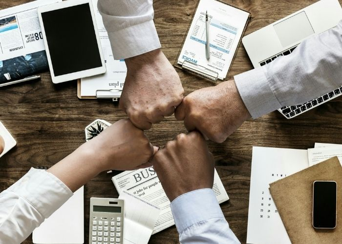 Image of employees fist-bumping to show strong work relationships.