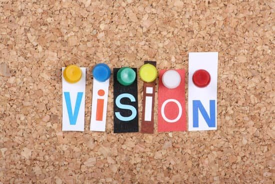 Image of the word vision tacked onto a cork board showing how to to make a vision board.