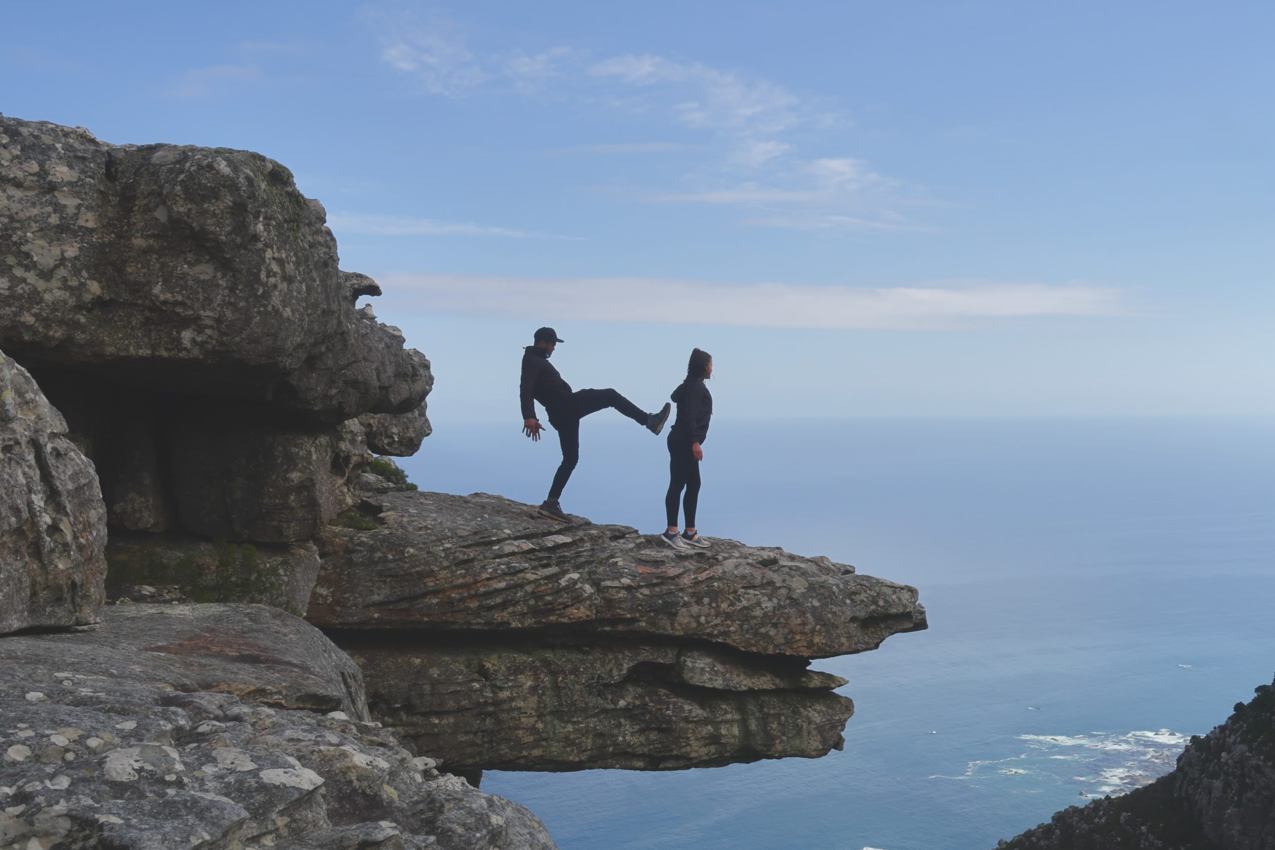 Image of person about to be pushed off cliff representing a boss, leader, supervisor, manger being too pushy.